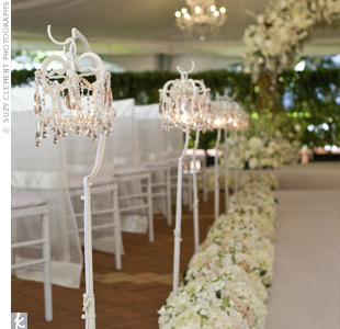Rows of stock and roses bordered the aisle while delicate chandeliers were hung from shepherd's hooks, giving off a romantic glow.