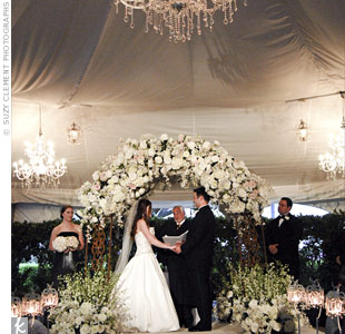 Guests couldnt miss the altar area, a raised platform under chandeliers. The couple exchanged vows beneath an arch decorated with flowers similar to the ones lining the aisle.