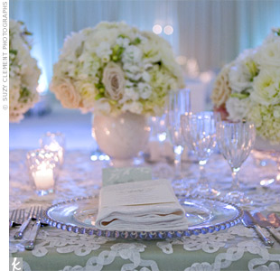 Bowls overflowing with white and pale-green flowers, like roses and hydrangeas, decorated the rectangular head table, which stood out from the round ones.