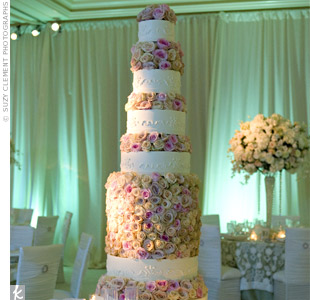 The main attraction in the green-lit reception room was the cake. A layer of fresh roses in pink and cream hues separated each tier of the towering dessert.