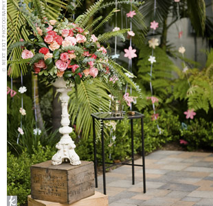 Hanging paper-flower garlands, roses in antique urns, and vintage wine crates incorporated the theme into the ceremony.