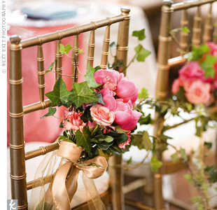 Bunches of pink and coral peonies, carnations, and roses marked the bride and groom's gold chairs.
