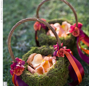 To match the weddings outdoor setting, the flower baskets were covered with moss. Orange and fuchsia ribbons coordinated with the vivid colors at the ceremony.