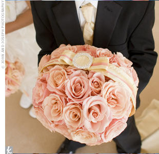 Jessica's friend's son carried a ring pillow made of peach-colored roses to match the bridesmaid bouquets and the other flowers.