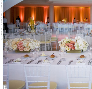 A combination of rectangular and round tables surrounded the dance floor. Behind, amber uplighting warmed up the airy, white space.