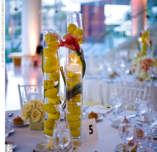To contrast with the coral-colored centerpieces, some reception tables had tall, cylindrical vases filled with lemons and wrapped with calla lilies.