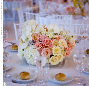 To add depth to the reception space, tall and short centerpieces alternated on the tables. The lower centerpieces were arrangements of roses, hydrangeas, orchids and calla lilies.