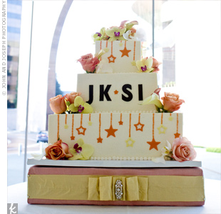 Jessica and Scott's fondant-covered wedding cake was decorated with the couple's initials and orange and yellow stars. Fresh roses and orchids on each tier added more color to the cake.