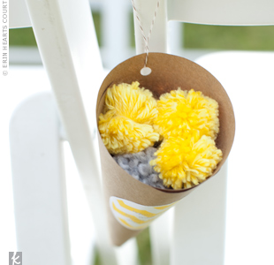 Cones made of kraft paper and filled with pom-poms Kelly had made hung from guests' chairs. Instructions on the signature yellow chevron paper asked guests to toss the pom-poms.