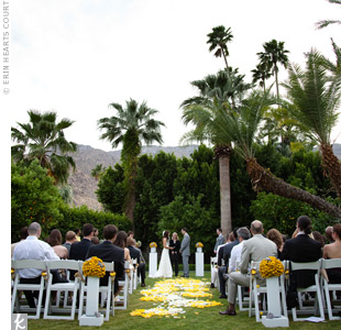 The ceremony took place at a private residence with a mountain backdrop. The couple's florist arranged white and yellow rose petals along the aisle in interlocking circles.