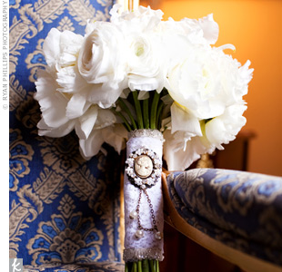 White satin, lace, a cameo, and pearls decorated Megans all-white bouquet, giving it an antique look.