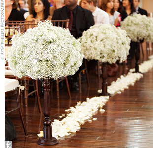 White rose petals lined the aisle and stood out against the dark, wood floors. Tall candlesticks sat beside every other chair along the aisle and held arrangements of babys breath.