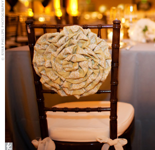 In contrast with the other tables, Megan and Jason's sweetheart table was covered in gray-blue linens. Fabric folded to look like flowers dressed up the backs of their chairs.