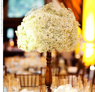 Conscious of the earth and their budget, the couple used the same tall candlesticks of baby's breath that lined the ceremony aisle as their reception centerpieces.