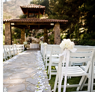 White and yellow flower petals lined the stone-paved aisle, and roses, hydrangeas, and orchids decorated the chairs along it.