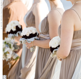 To coordinate with their color-block dresses, the bridesmaids carried multicolored bouquets of white garden roses surrounded by rings of chocolate cosmos and lamb's ear.