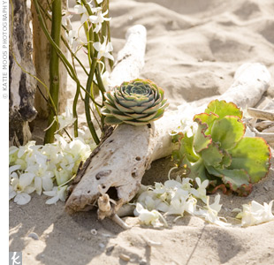 To make their beach ceremony more chic, the couple added orchids and greenery to driftwood.
