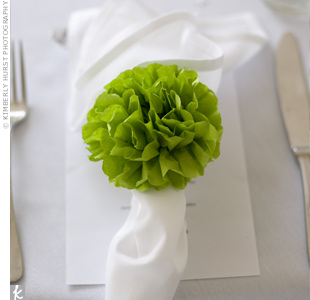 The bride added pops of color to the white place settings with tissue-paper pompom napkin rings she made herself.