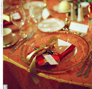 Red Moleskine notebooks, the bride's favorite kind, and personalized pens waited at guests' seats. Gold ribbon gave the gifts a polished look.