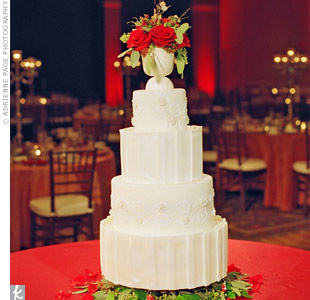 Inspired by the bride's beaded gown with a crumbcatcher neckline, the cake had folds of icing and intricate patterns. Greenery and red flowers worked in the holiday theme.