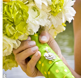Amy's bouquet was filled with mums, daisies, ranunculus, and hydrangeas. The stems were wrapped with a green-and-yellow polka-dot ribbon and accented with a four-leaf clover charm.
