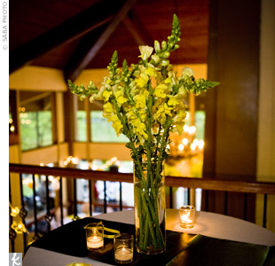 An arrangement of bright yellow snap dragons in tall cylinder vases towered over the flickering votives below, giving the tables a dramatic focal point.