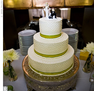 Yellow and green ribbons brightened up the cake, while lots of white dots gave it texture. A whimsical bride and groom topper reflected the couple's fun style.