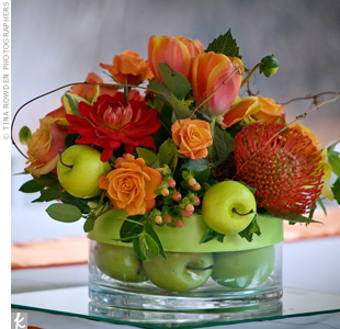 At the center of each table sat a glass vase filled with either green apples or lemons. An arrangement of roses, protea and tulips represented the couple's color palette.