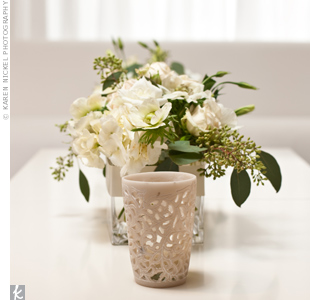 Smaller, low-lying centerpieces featured a variety of white roses, tulips, and seeded eucalyptus. For an even more romantic vibe, votive candles flickered around the centerpieces.