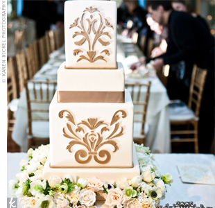 An opulent combination of fresh and sugar flowers encircled the bottom tier of the couples beautiful cake. The confection was etched with an elegant pattern on two of the tiers.