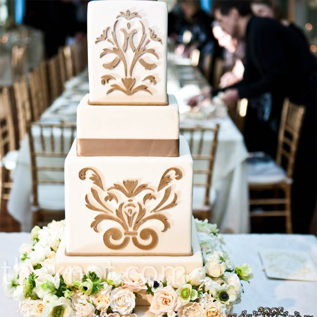 An opulent combination of fresh and sugar flowers encircled the bottom tier of the couple's beautiful cake. The confection was etched with an elegant pattern on two of the tiers.