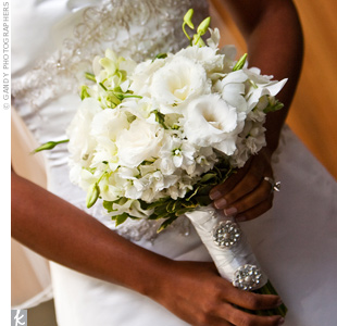White dendrobium orchids, hydrangeas, stock, and lisianthus filled out the traditional white bouquet, while white satin ribbon and crystal brooches adorned the stems.