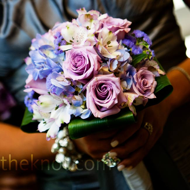 To complement their charcoal gray dresses, the bridesmaids carried purple hydrangeas, lavender stock, lisianthus, and lavender cymbidium orchids.
