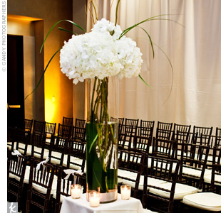 Columns draped in white fabric marked the aisles in the ballroom where the ceremony was held. Tall cylinders filled with white hydrangeas and curly willow topped each column.