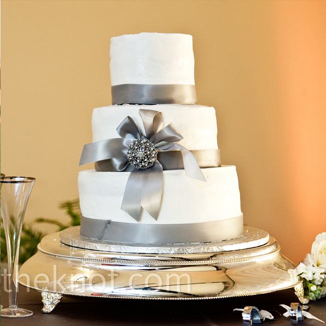 Silver ribbon, a decorative bow and a crystal brooch transformed a simple three-tiered buttercream cake into an elegant centerpiece.