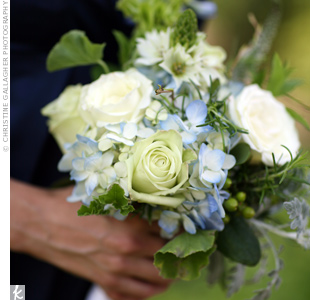 The blue hydrangea blooms in the bouquets matched the bridesmaids navy blue dresses, while white garden roses and green hypericum berries accented the look.