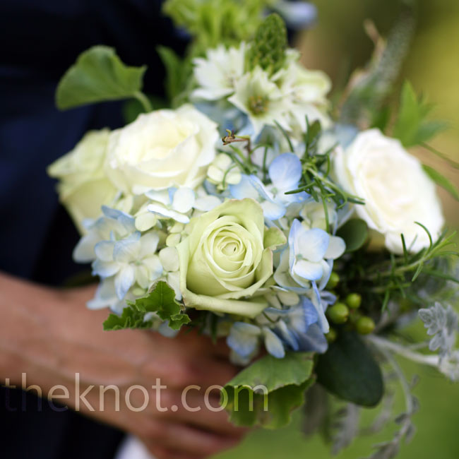 The blue hydrangea blooms in the bouquets matched the bridesmaids' navy blue dresses, while white garden roses and green hypericum berries accented the look.