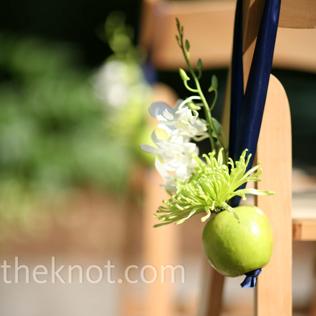 Green apples added an earthy touch to the green Fuji mum and white dendrobium orchid arrangements that hung from the ceremony chairs.