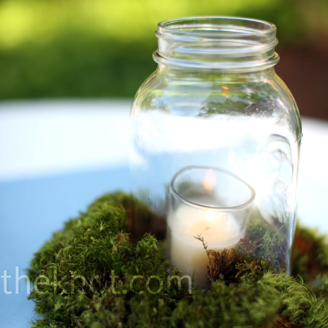 Recycled Mason jars held flickering candles and sat on beds of green moss. Soft blue table linens provided a burst of color beneath the earthy arrangements.