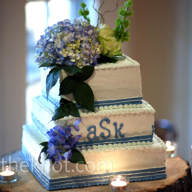 The bride's father found a tree stump and cut it into the perfect platform for the couple's three-tiered square cake. Kristi and Adam turned to a friend-of-a-friend to bake their monogrammed confection topped with fresh flowers.