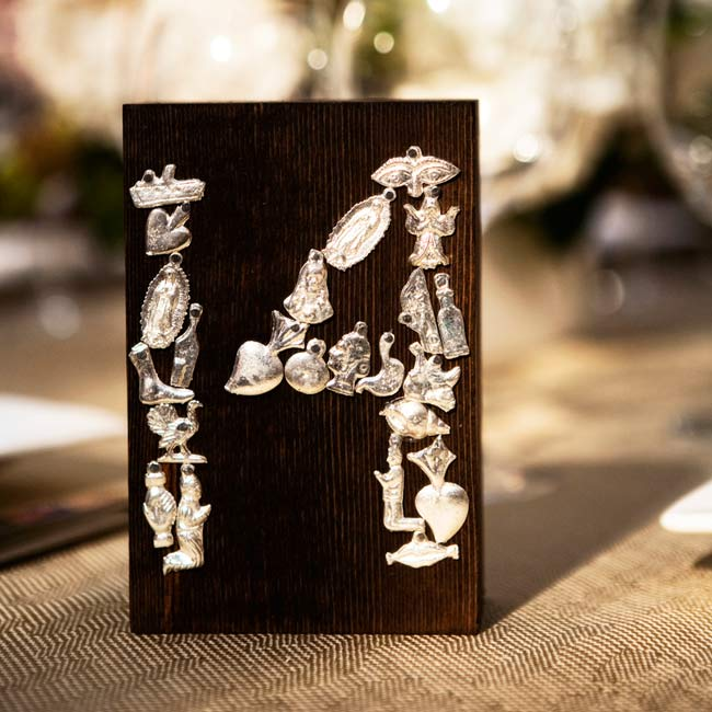 For a clever twist on table cards, Alison formed the table numbers out of Mexican charms attached to a block of wood.