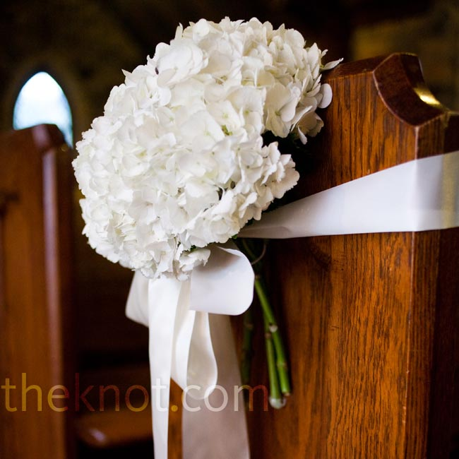 White hydrangeas were tied to the ends of the pews with white, flowing ribbon