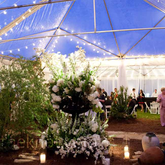 Guests walked through the tented courtyard and were seated near a black iron fountain filled with white floral décor and greenery.