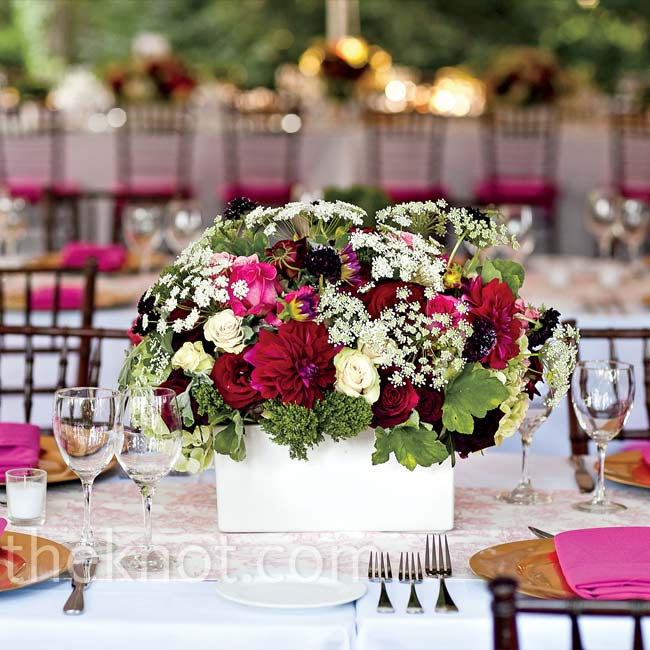 Arrangements overflowing with roses, dahlias and Queen Anne's lace were dressed down by a simple white, ceramic container.