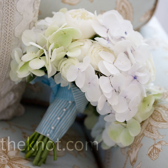 A seersucker-like wrap was a beachy accent to the bride's bouquet of hydrangeas, peonies, and ranunculus.