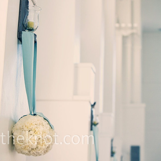 The couple made the church their own by hanging carnation pomanders from the wall sconces. The ribbon brought the ocean into the all-white church.
