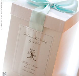 Out-of-town guests got a glimpse of the wedding's sea-inspired color palette from their welcome boxes. The logo on the outside appeared on many of the other wedding elements.