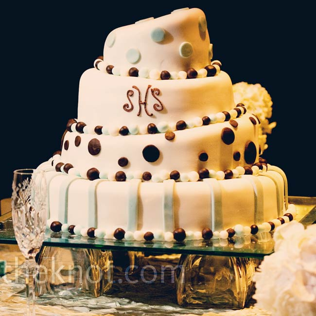 Each tier of the couple's topsy-turvy wedding cake had a different design. The mixed styles worked because they all incorporated the same blue, brown, and white color scheme.