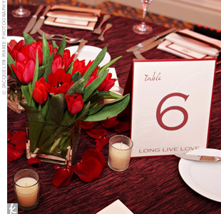 Some tables were decorated with roses, hypericum berries, lilies and tulips in a grouping of square vases. Scattered rose petals and white votives contrasted with the crinkled linens.
