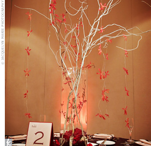 Some tables had tall curly willow branches with red orchids. Scattered rose petals and red stones in the vases worked in even more of the signature hue.